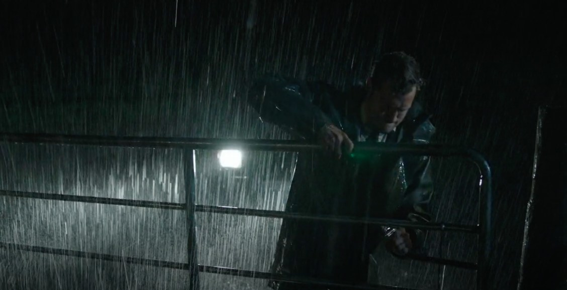 Jamie Dornan's character, Anthony, opening a metal gate in the rain