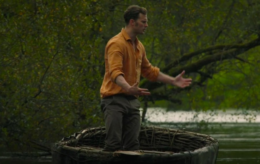 Anthony standing in a boat and gesturing to the air.