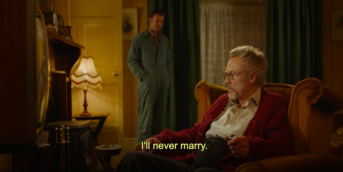 """Tony sits on a chair in the living room, Anthony stands by the door saying """"I'll never marry"""""""