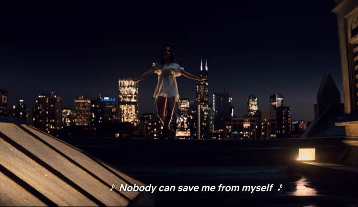 """Cassie Shore dancing on the ledge in a white dress; chicago skyline in the background. """"Nobody can save me from myself"""" lyric."""