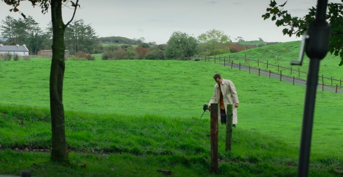 Anthony wears a raincoat and uses a metal detector in a field
