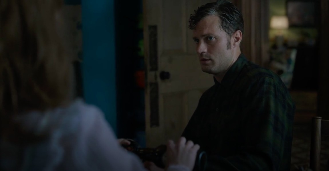 A wet Anthony looks at Rosemary as she pours him a drink in her kitchen