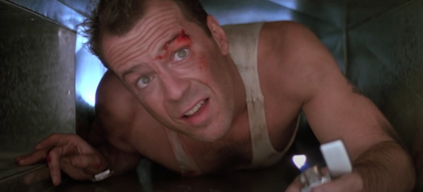 John McClane in a vent with a lighter