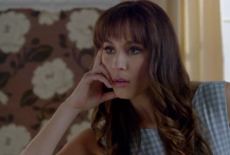 Alex Drake leaning on her hand looking bored