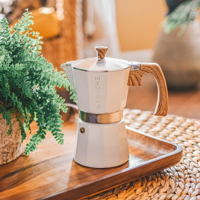 White espresso maker on a wooden tray