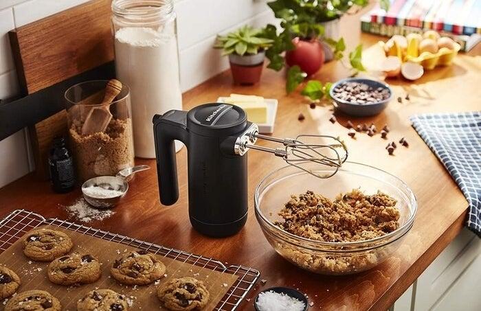 Hand mixer standing up beside cookie dough