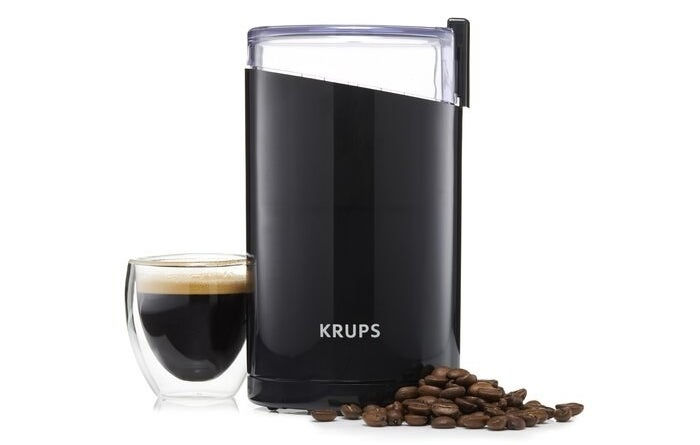 Electric coffee grinder with coffee beans and an espresso beside it