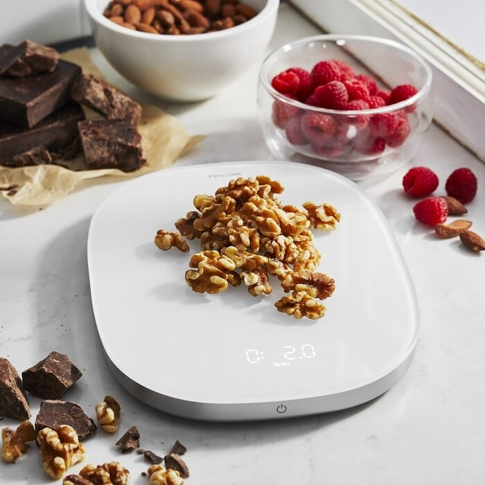 A kitchen scale with walnuts on it.