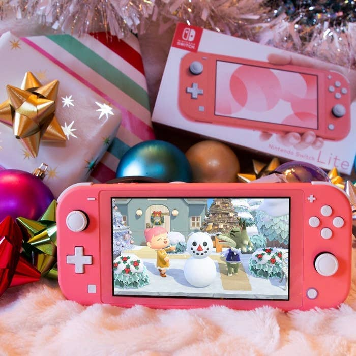 a pink nintendo switch lite with animal crossing on the screen