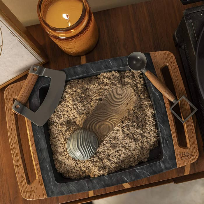 a wooden platter with marbled material in the middle filled with sand