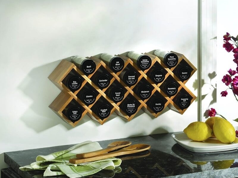 the kamenstein criss cross 18 piece spice rack mounted on a kitchen wall