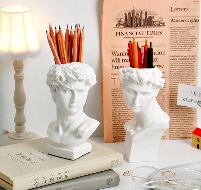 two stylish david pen holders on a desk holding pens and pencils