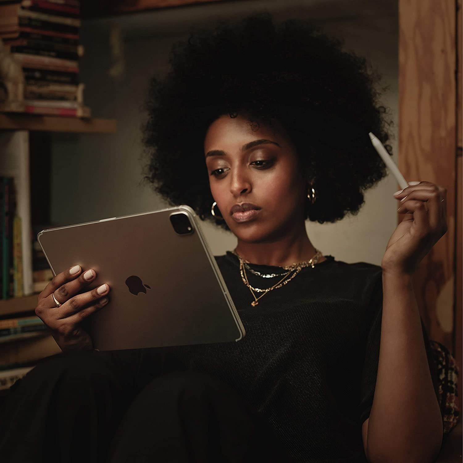 a model using the apple pencil while holding an ipad