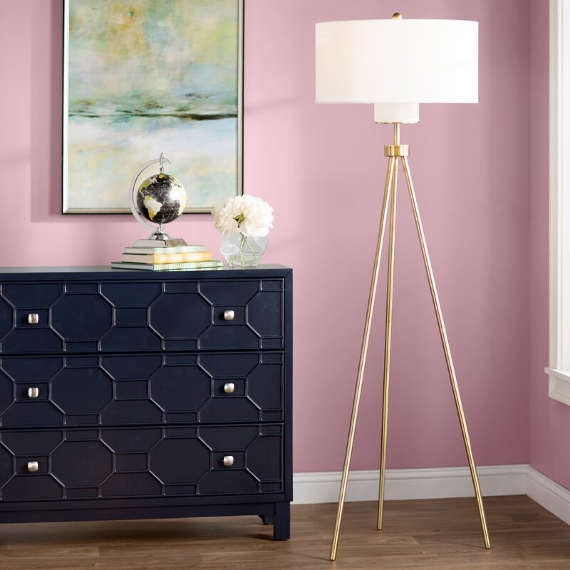"the willa arlo interiors Floretta 66"" Tripod Floor Lamp next to a dresser"