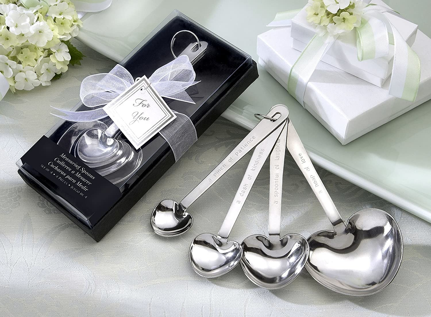 """Four heart-shaped measuring spoons with messages like """"a pinch of patience"""" and """"a dash of kindness"""" on them"""