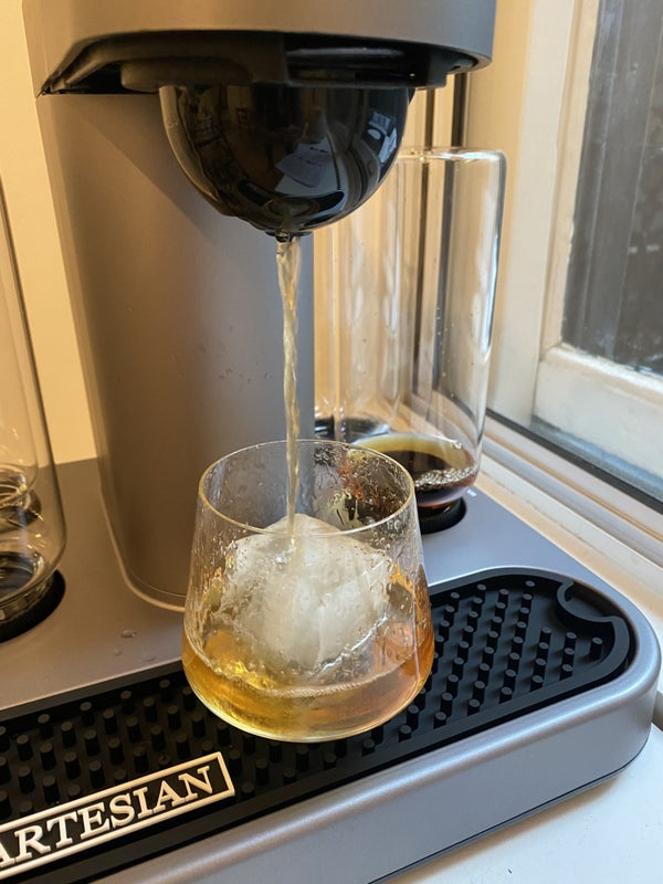 A picture from BuzzFeed Editor Hannah Loewentheil of the machine brewing a cocktail into a glass