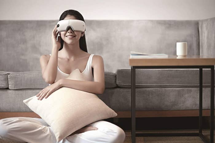 A person wearing the eye massager and sitting in front of a sofa.