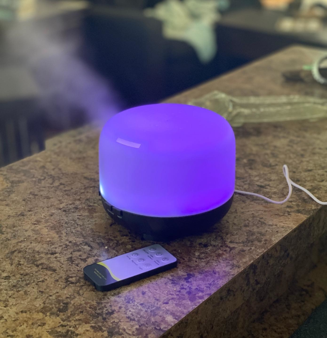 a reviewer's essential oil diffuser glowing purple