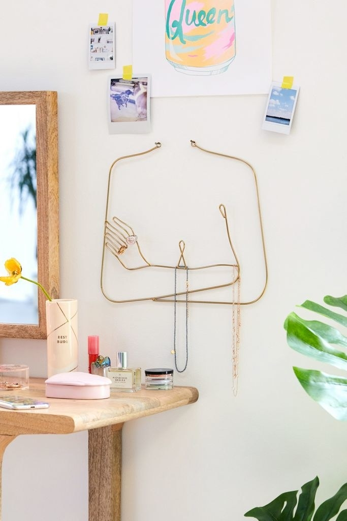 the femme wall hanging mounted on a wall, storing jewelry