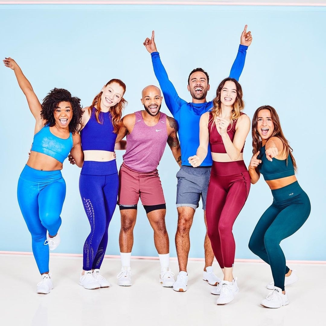 Six instructors in athletic wear smiling and posing together