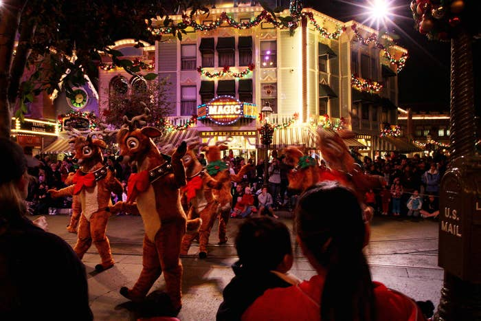 Visitors watch a Christmas parade along Main Street at Disneyland in Anaheim