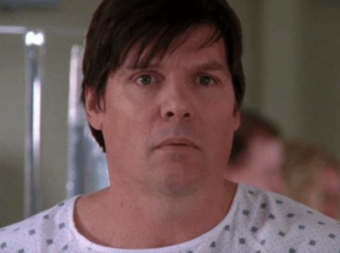 Dan wearing a hospital gown and looking shocked