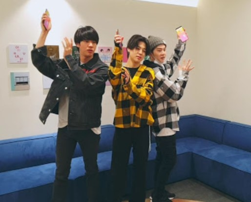 Jin, Jimin, and Suga play a dance game in front of a couch