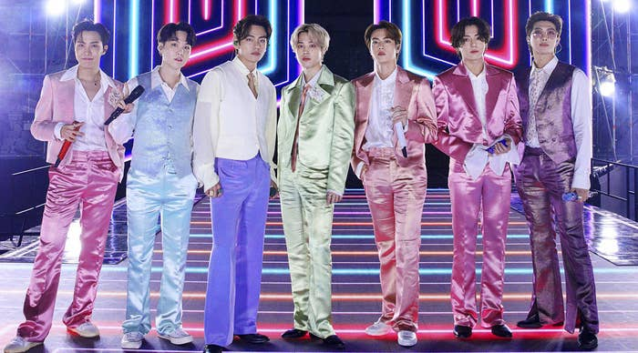 BTS wears colourful satin suits standing in a line on a lit-up stage