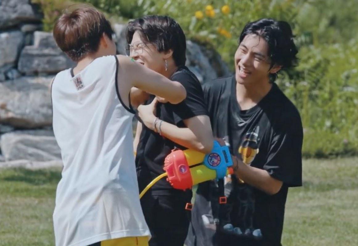 J-Hope, Jimin, and V play with water guns.