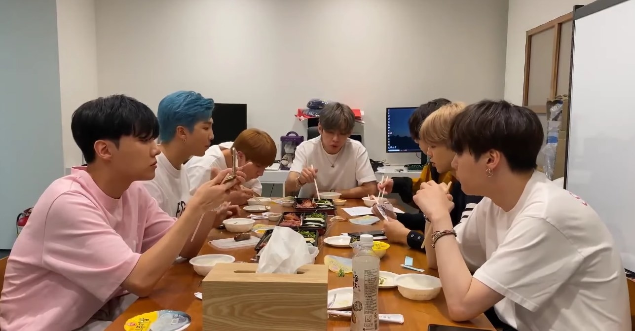 The BTS members sit around a meeting table eating and talking