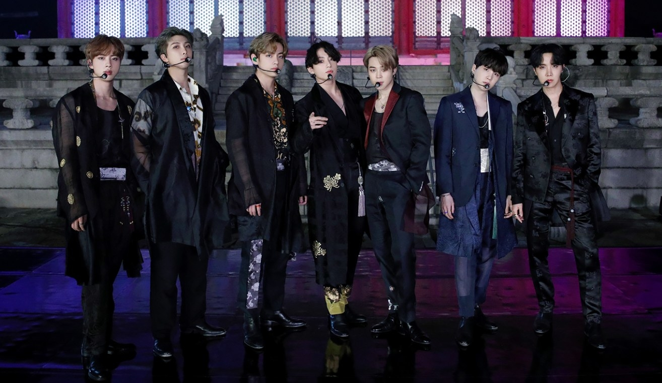 BTS wear traditional Korean clothes and stand on stage in front of a palace
