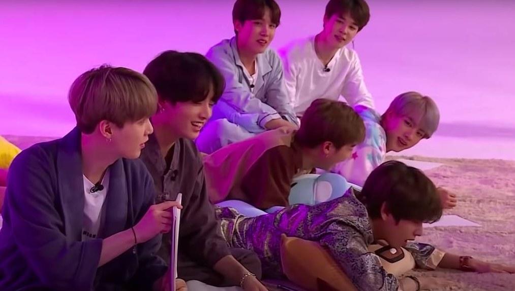 The BTS members wear pyjamas and lie on a rug
