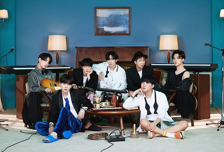 Promo photo for BE in which BTS sit in a bedroom, surrounded by instruments