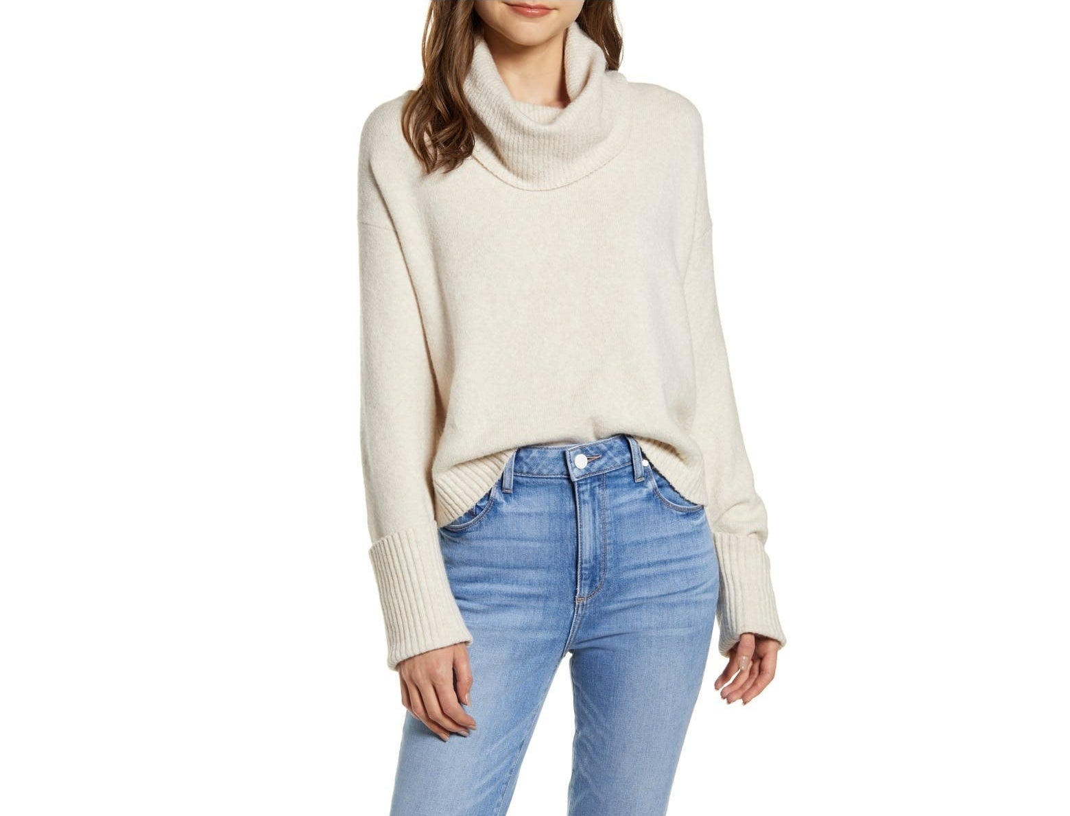 Model wearing the cream sweater tucked into jeans