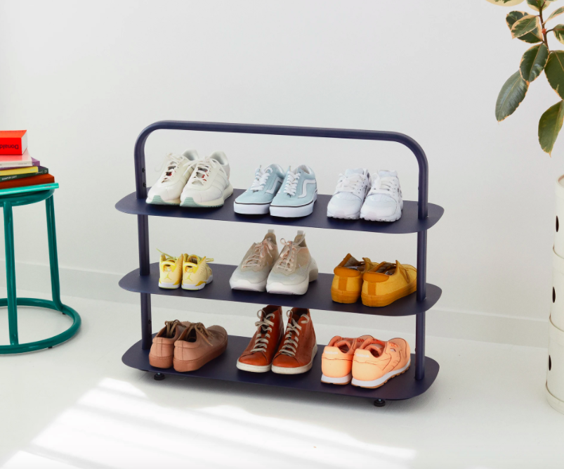 Three-tiered blue shoe rack with nine pairs of shoes displayed