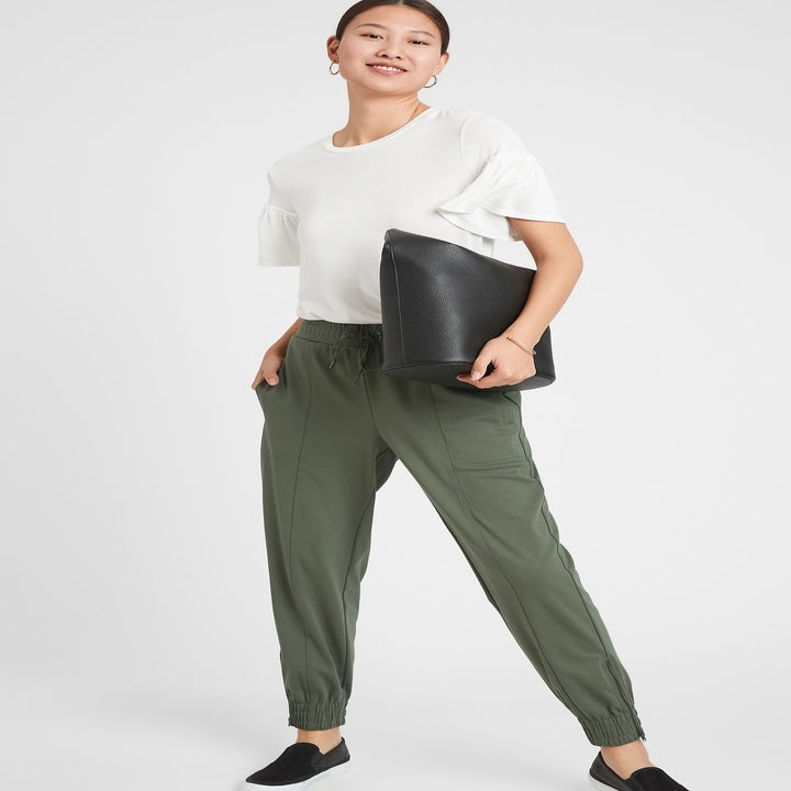model wearing zip-cuff knit joggers in green paired with a white shirt and black slip on shoes