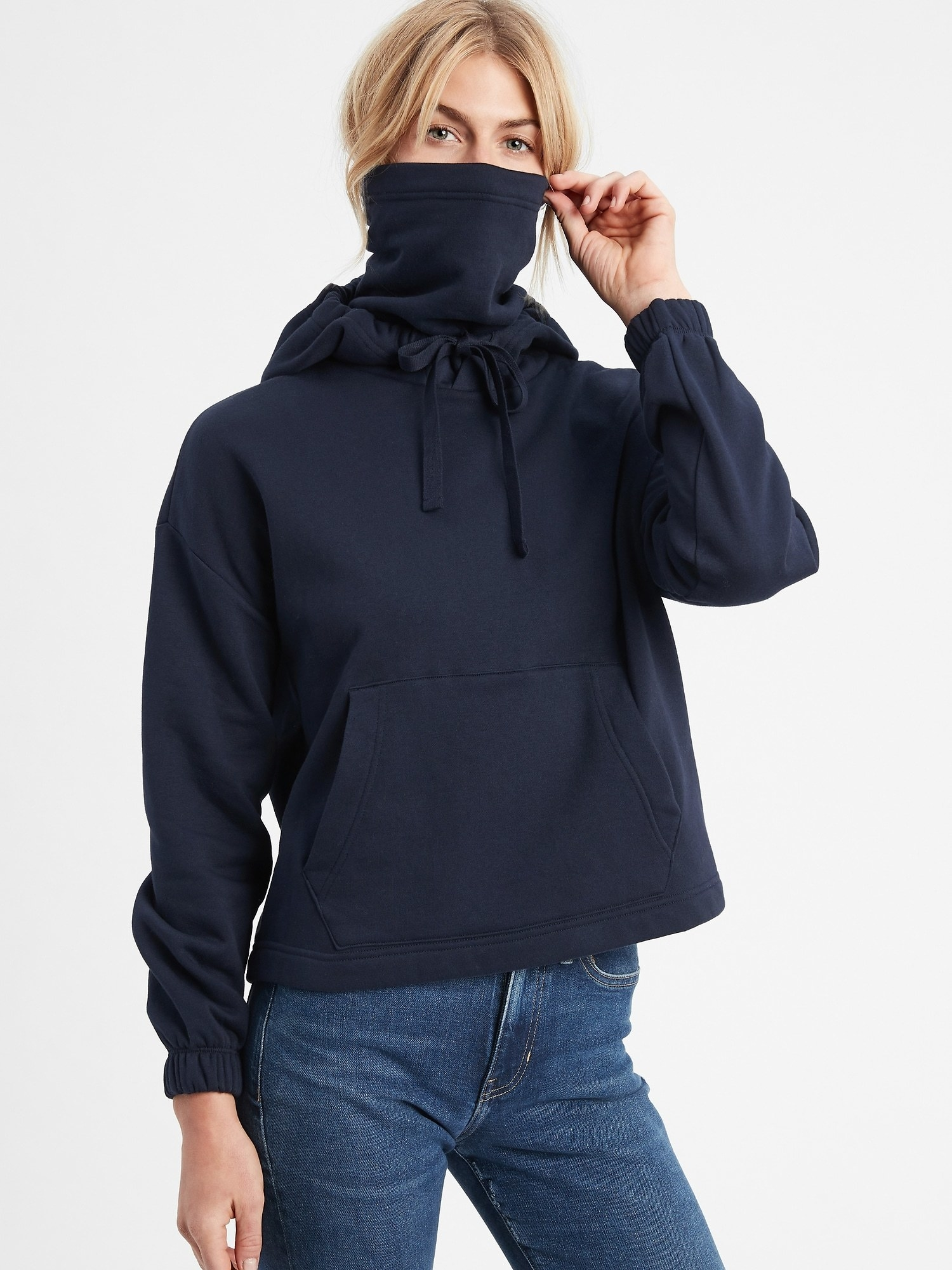 model wearing sweatshirt in black with face covering pulled over their face