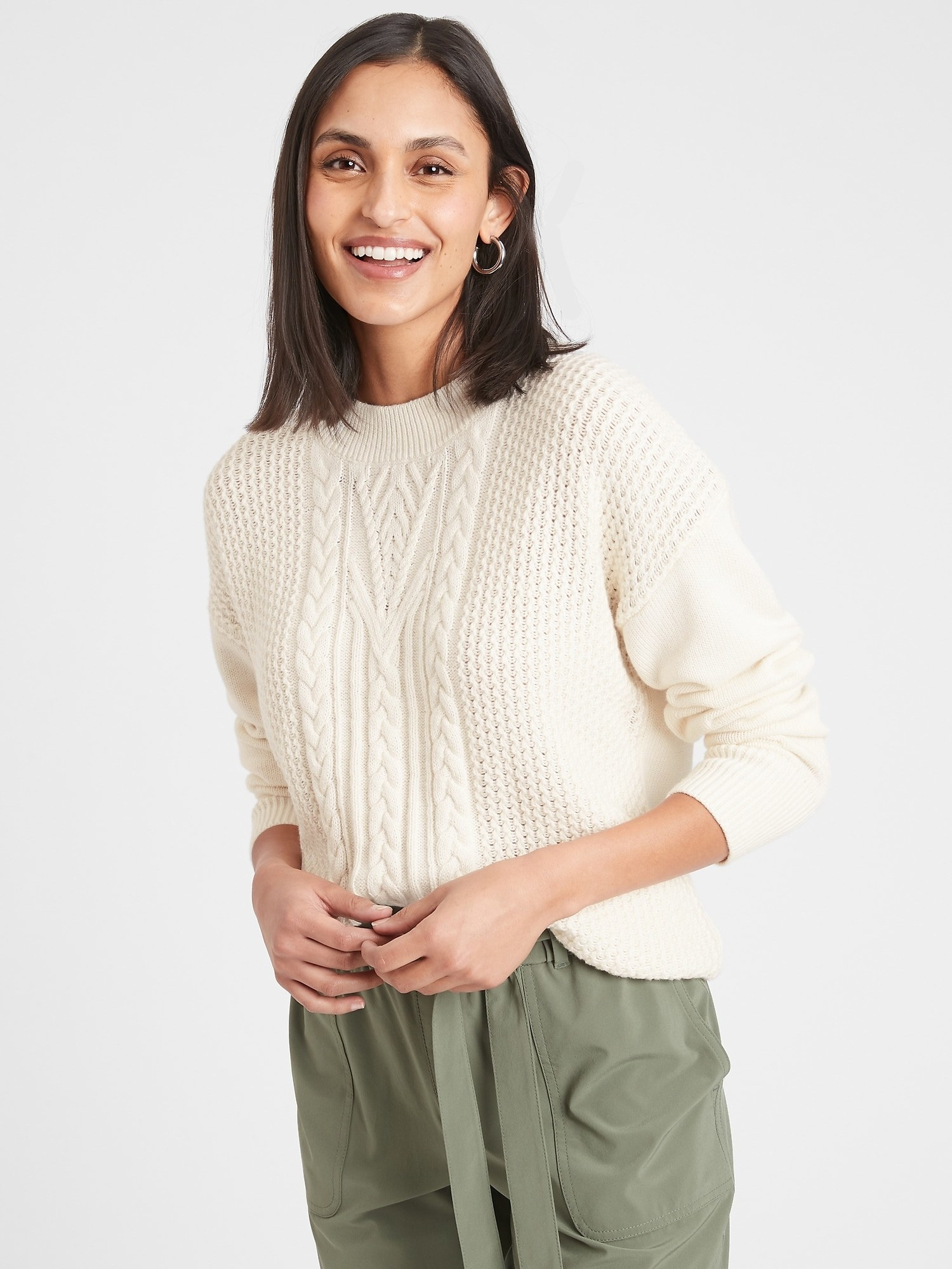 model wearing cable-knit sweater in off white
