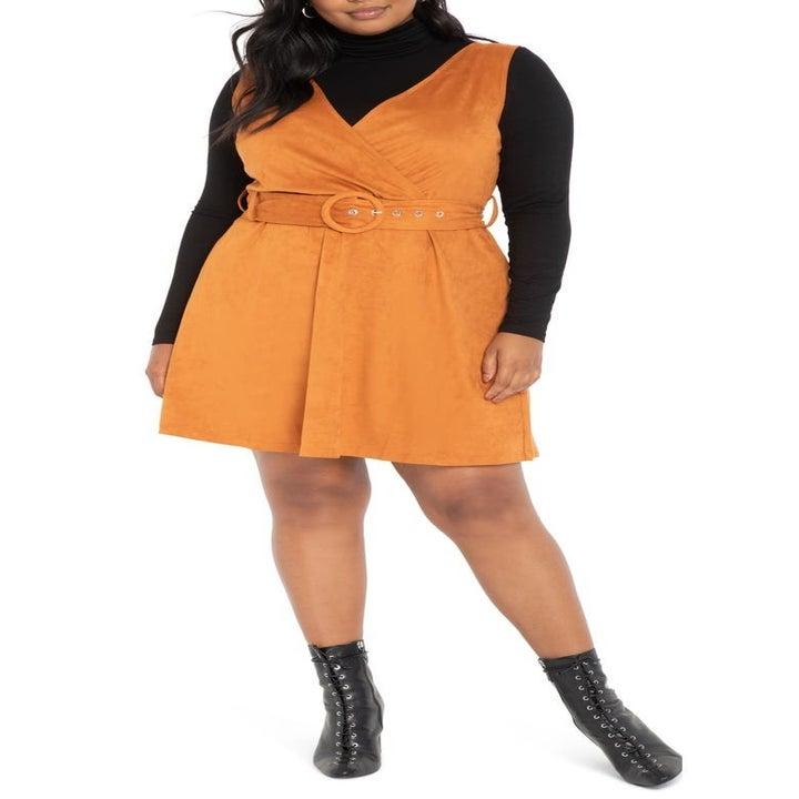 Model wearing the orange belted dress over a black long-sleeve turtleneck