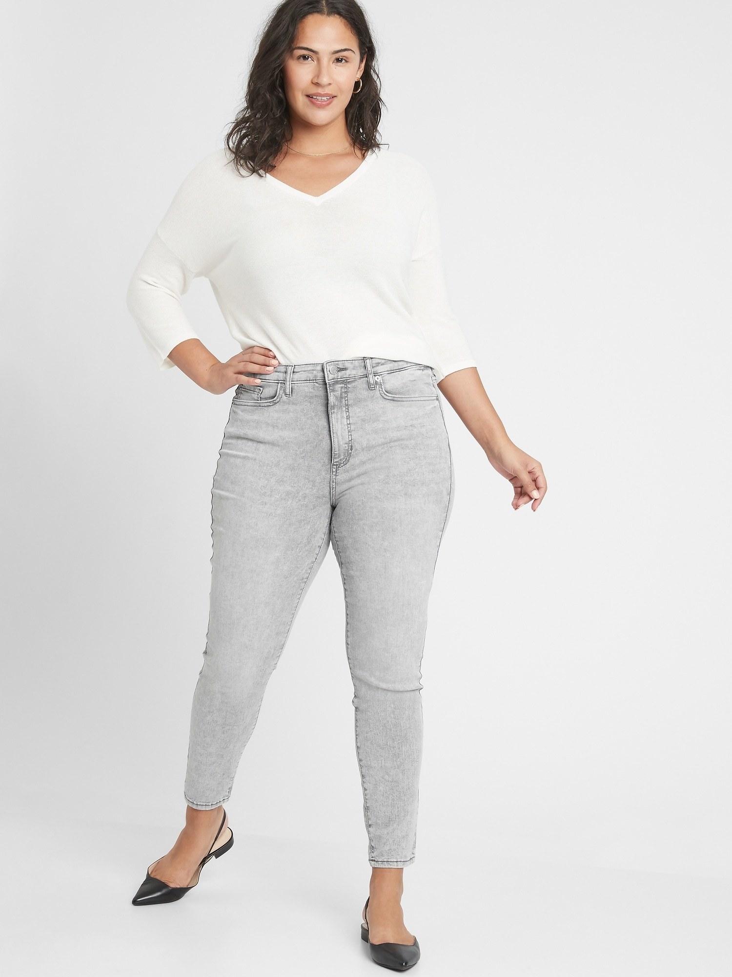 model wearing grey acid wash jeans in curvy fit