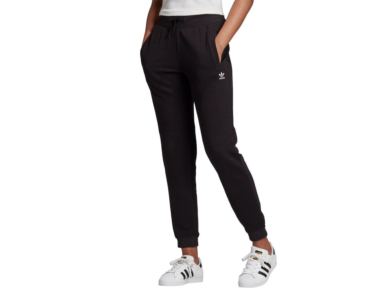 Model wearing the black sweatpants with a mini Adidas logo underneath the side pocket