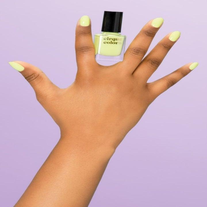 Model holding neon green nail polish