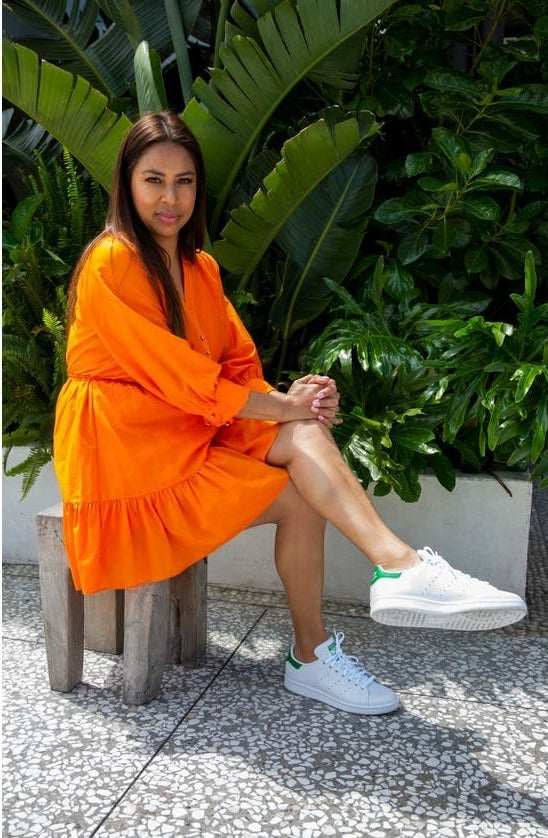 Model wearing the white sneakers with green backings