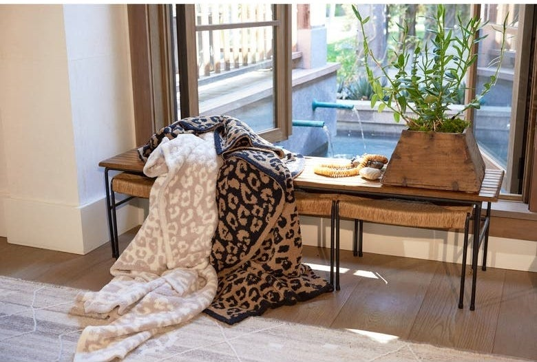 Two blankets on a bench, one white and pink leopard print and one tan and black leopard print