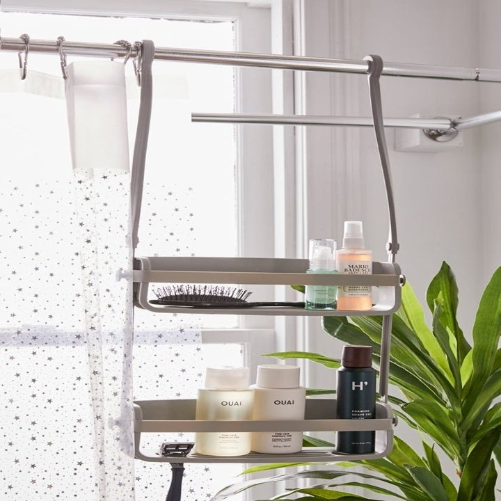 caddy hanging on shower curtain bar with the two arms parallel