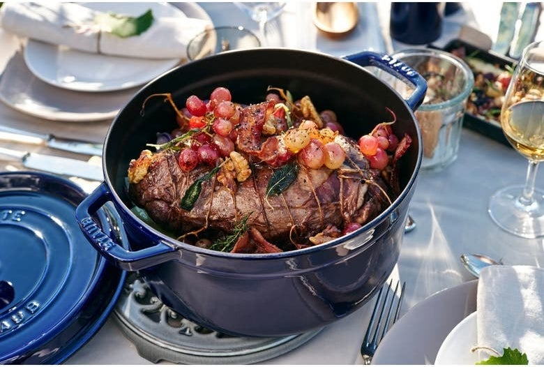 A hunk of meat and vegetables inside a blue cocotte