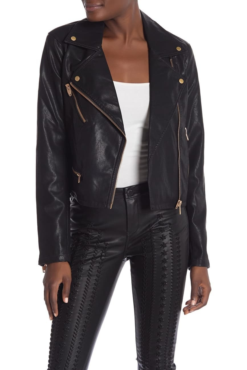 a model wearing the black faux leather jacket