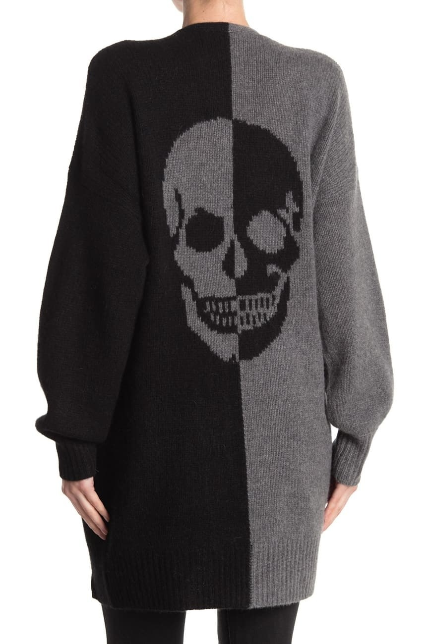 a model in a sweater that is black on one half and gray on the other with a skull in the middle