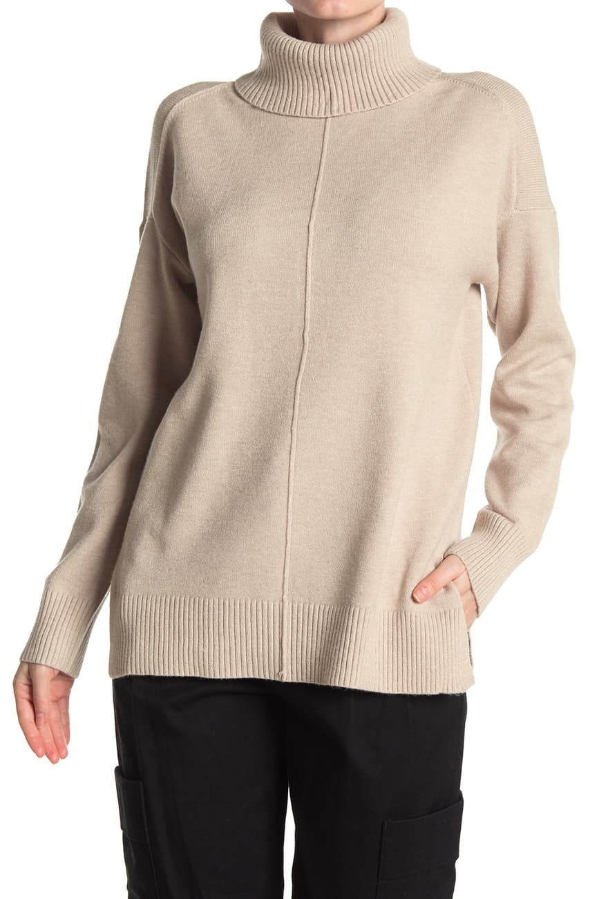 a model in a tan turtleneck sweater