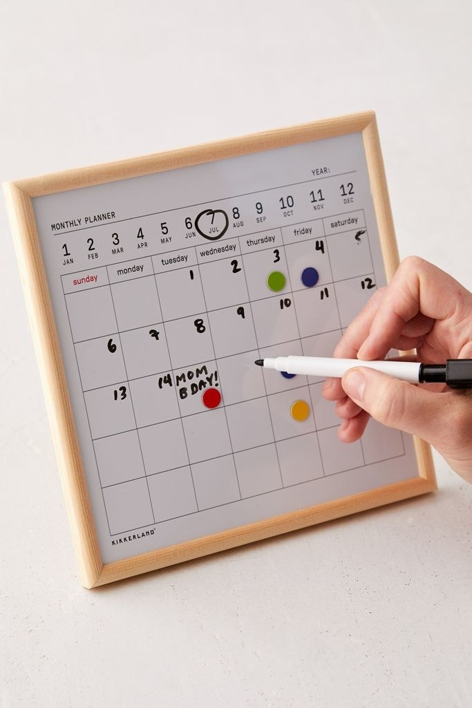 white dry erase with light wood frame with blank squares for you to write the dates
